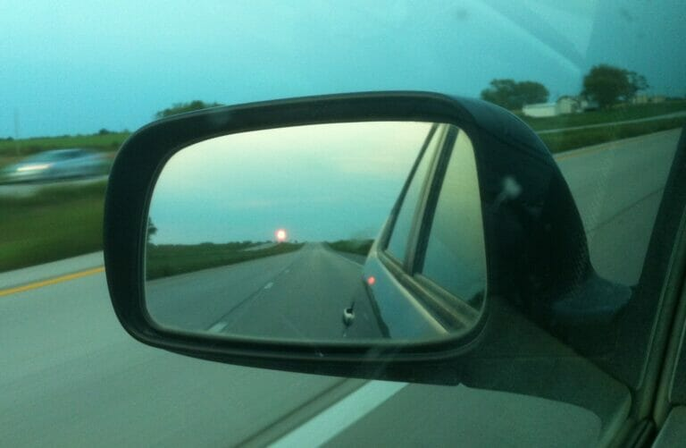 Driving seeing the setting sun in the rear view mirror.